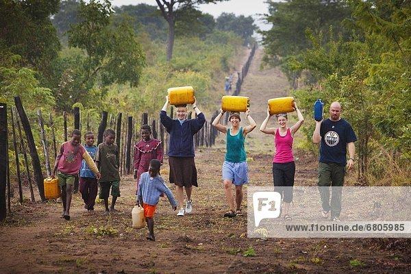 hoch  oben  Wasser  Mensch  Menschen  tragen  Menschengruppe  Menschengruppen  Gruppe  Gruppen  Fernverkehrsstraße  Kanne  Afrika  Mosambik