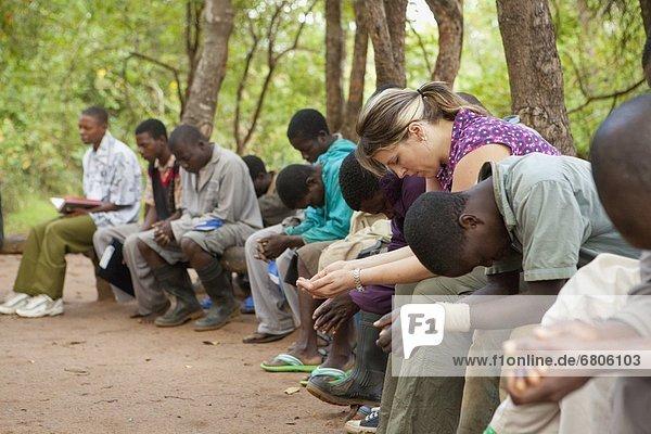 Außenaufnahme  sitzend  Zusammenhalt  Mensch  Menschen  Menschengruppe  Menschengruppen  Gruppe  Gruppen  Gebet  Afrika  Mosambik