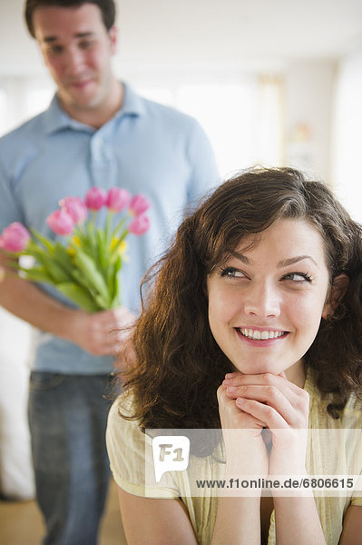 Woman smiling  man with flowers in background