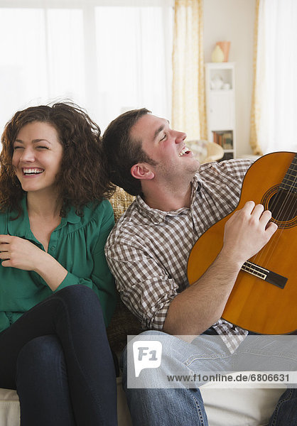 Couple sitting on sofa  man playing guitar