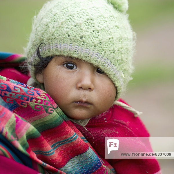 A Baby Wearing A Green Hat  Peru