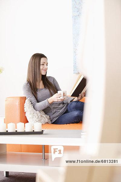 Frau  Couch  lächeln  jung  vorlesen