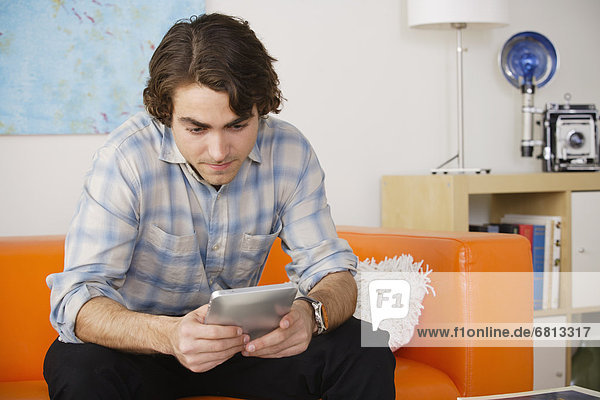 sitzend benutzen Mann Couch jung Tablet PC