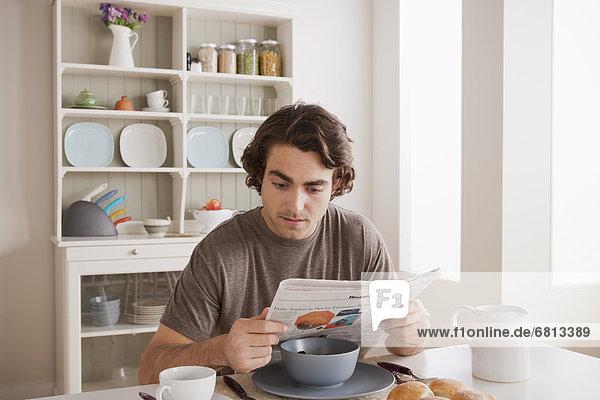 Mann  jung  Frühstück  Zeitung  vorlesen