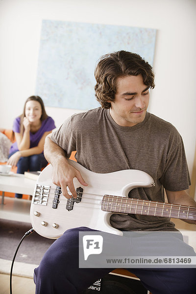Young man playing electric guitar  young woman in background