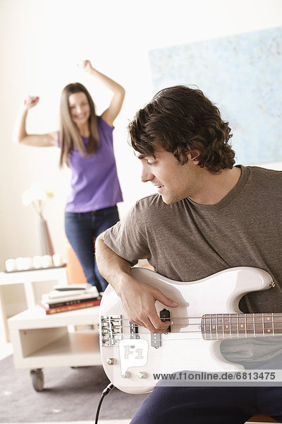 Young man playing electric guitar  young woman dancing in background