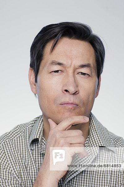 Studio portrait of mature man with hand on chin
