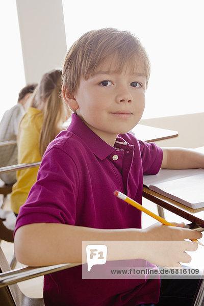 Schoolboy holding pencil in classroom