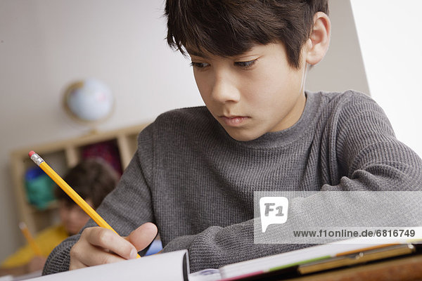 Writing boy (12-13) with boy (10-11) in background