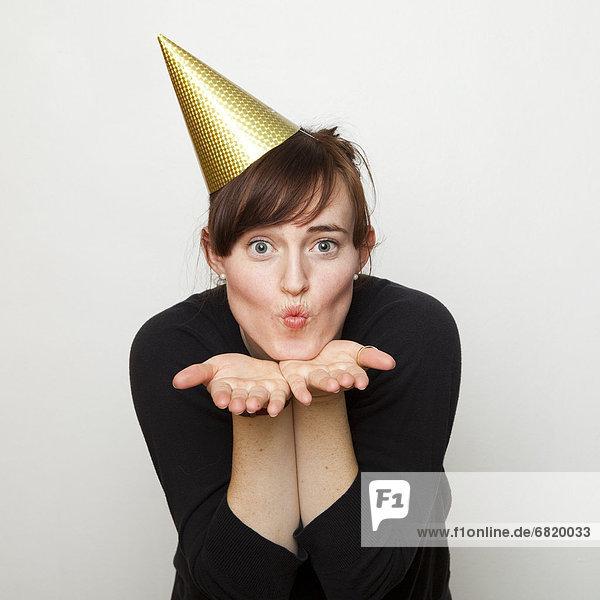 Frau  Party  blasen  bläst  blasend  küssen  Hut  jung  schießen  Studioaufnahme