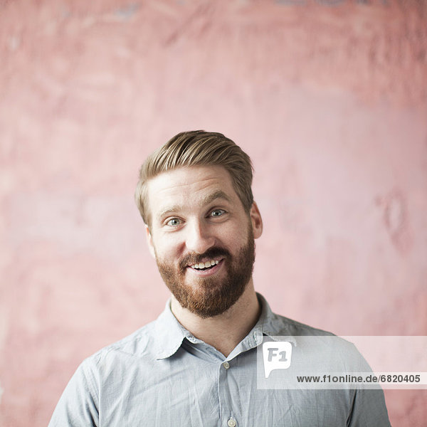 Portrait of laughing young man against pin background