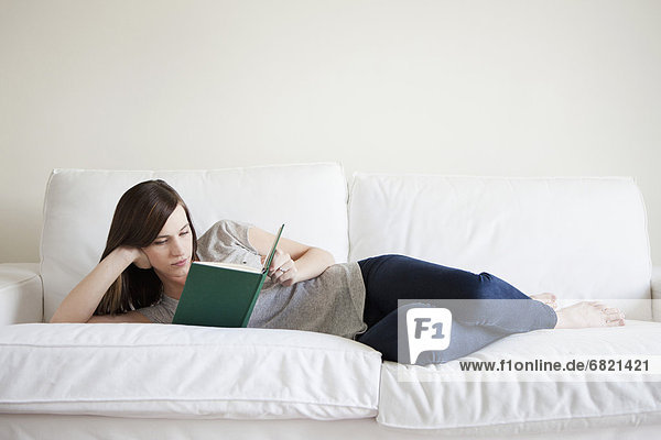 Young woman reclining on bed  reading book