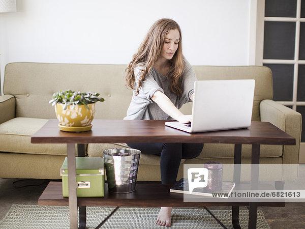 sitzend  benutzen  Attraktivität  Frau  Notebook  Couch  jung