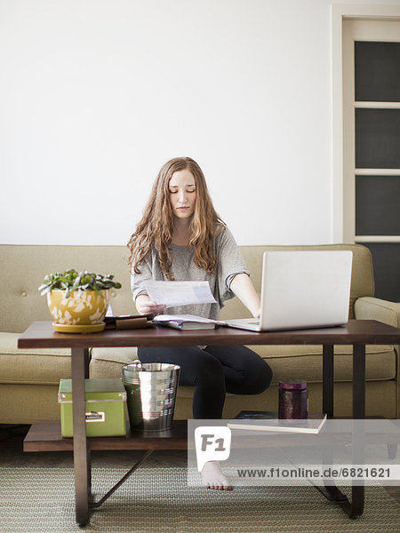 Young attractive woman using laptop while sitting on sofa