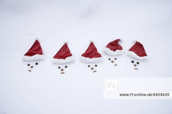 Faces in snow wearing Santa hats