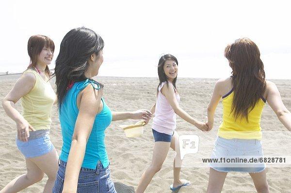 Four friends walking on the beach