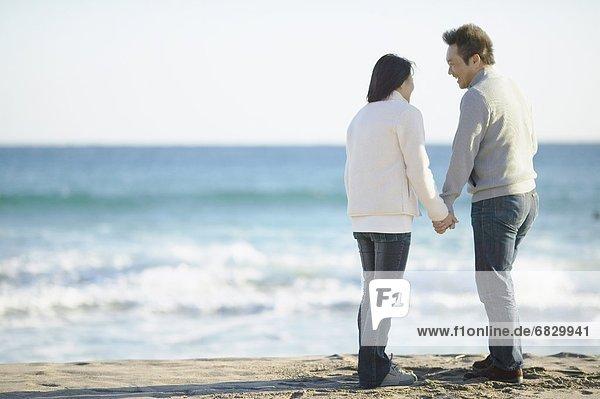 Paar hält hände am Strand