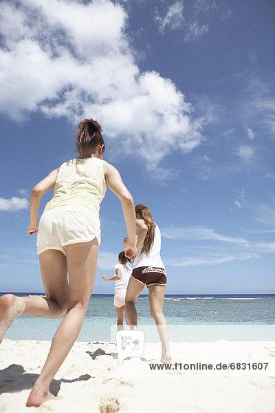 Young women running on beach,  Guam,  USA