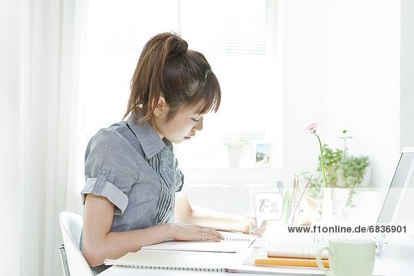 Young woman sitting at a desk and using a laptop