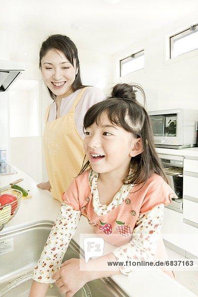 Mutter und Tochter in Küche kochen