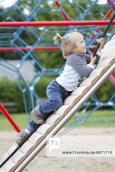 Blondes Mädchen klettert auf einem Spielplatz
