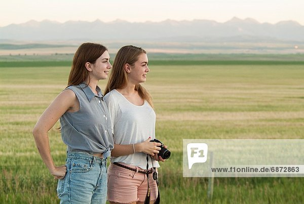 Two sisters  16 and 20  stand near a field in southern Alberta  Canada. Two sisters  16 and 20  stand near a field in southern Alberta  Canada
