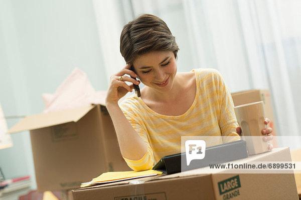Junge Frau auf dem Handy  mit digitalem Tablett auf Umzugskartons