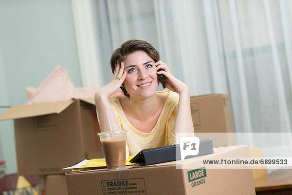 Junge Frau am Handy beim Umzug
