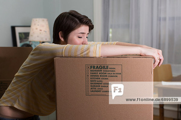Tired young woman resting on moving box