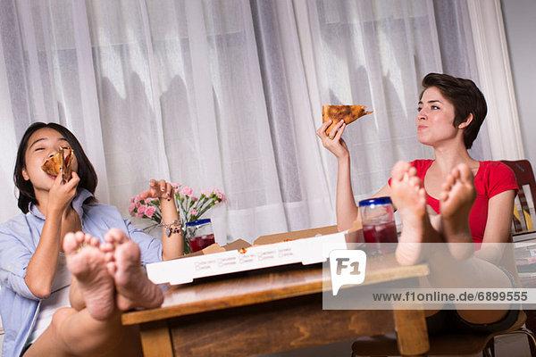 Freundinnen genießen Pizza zum Mitnehmen