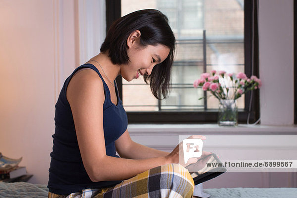 Young woman sitting on bed  using digital tablet