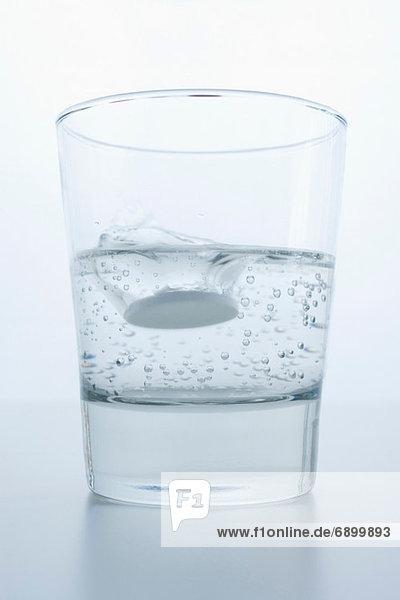 Pille im Glas Wasser