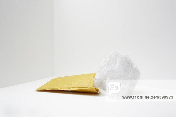 Gepolsterter Umschlag mit Kunststoffaustritt