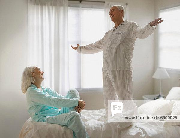 Seniorenpaar  das auf dem Bett herumalbert.
