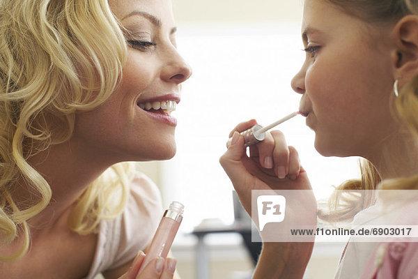 Mother Applying Lip Gloss on Daughter