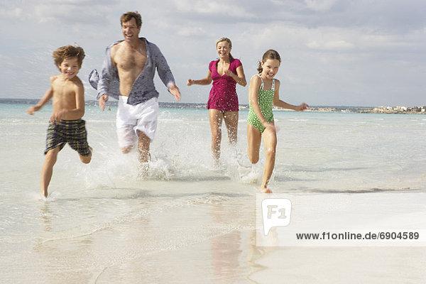 Family Running along Beach  Majorca  Spain