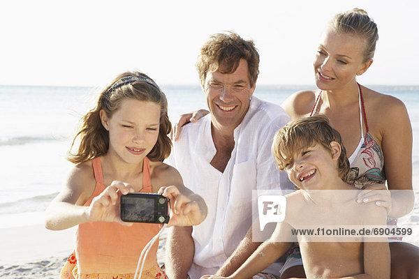 Girl Taking Portrait of Family on Beach  Majorca  Spain