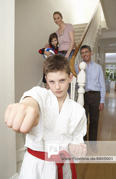 Boy in Karate Gi With Family in Background