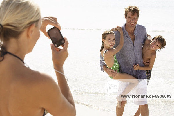 Woman Taking Picture of Husband with Children on Beach  Majorca  Spain