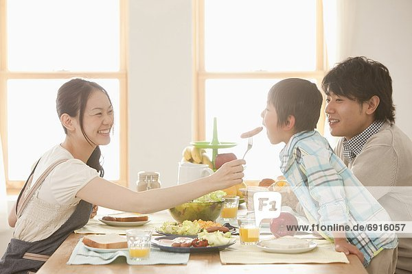Mother Offering Sausage to Son  Father Watching