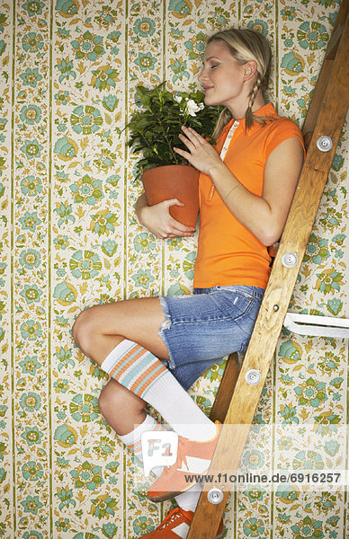 Woman Sitting on Ladder  Holding Plant