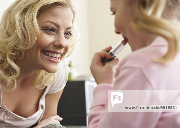 Girl Putting on Lipstick with Mother