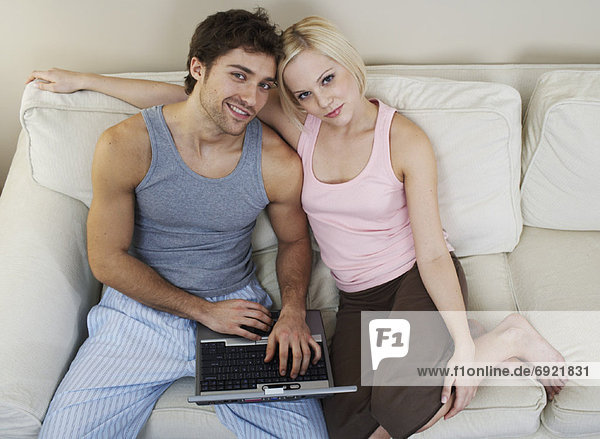 Couple with Laptop Computer on Sofa