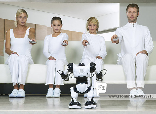 Portrait of Family Sitting on Sofa  Using Remote Controls on Robot