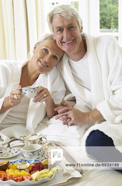 Bett reifer Erwachsene reife Erwachsene essen essend isst Frühstück