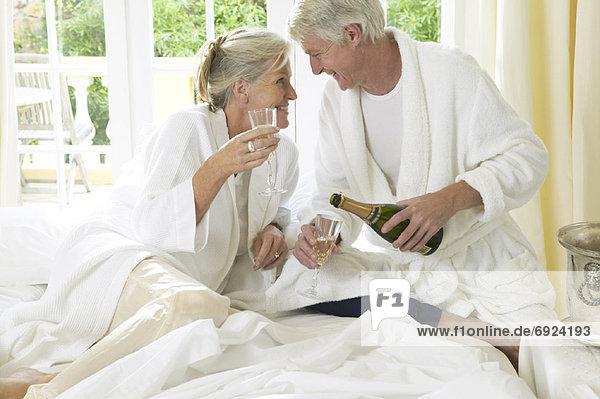 Bett reifer Erwachsene reife Erwachsene trinken Champagner