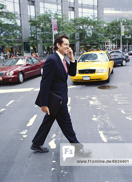 Businessman with Cellular Phone Crossing Street
