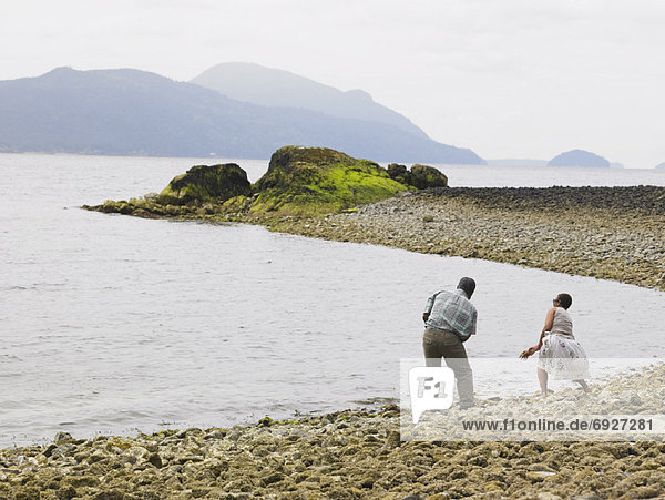 Couple Skipping Stones over Water