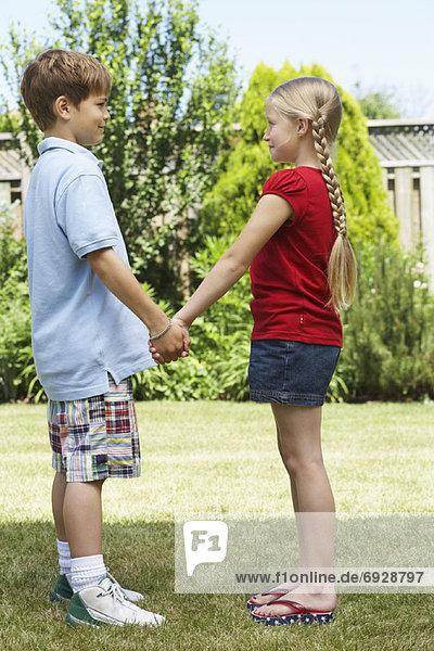 stehend  Junge - Person  halten  Garten  Seitenansicht  Mädchen  Hinterhof