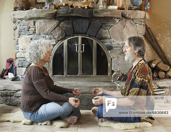 Hippie Couple Meditating in Front of Fireplace